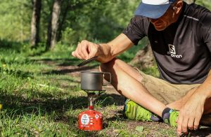 Man sat on ground with camping stove