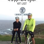 Two cyclists at Land's End Sign
