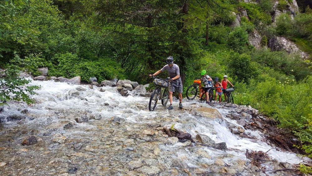 pushing bikes through a stream