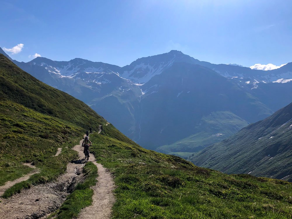 cyclists on path traversing around a mountain