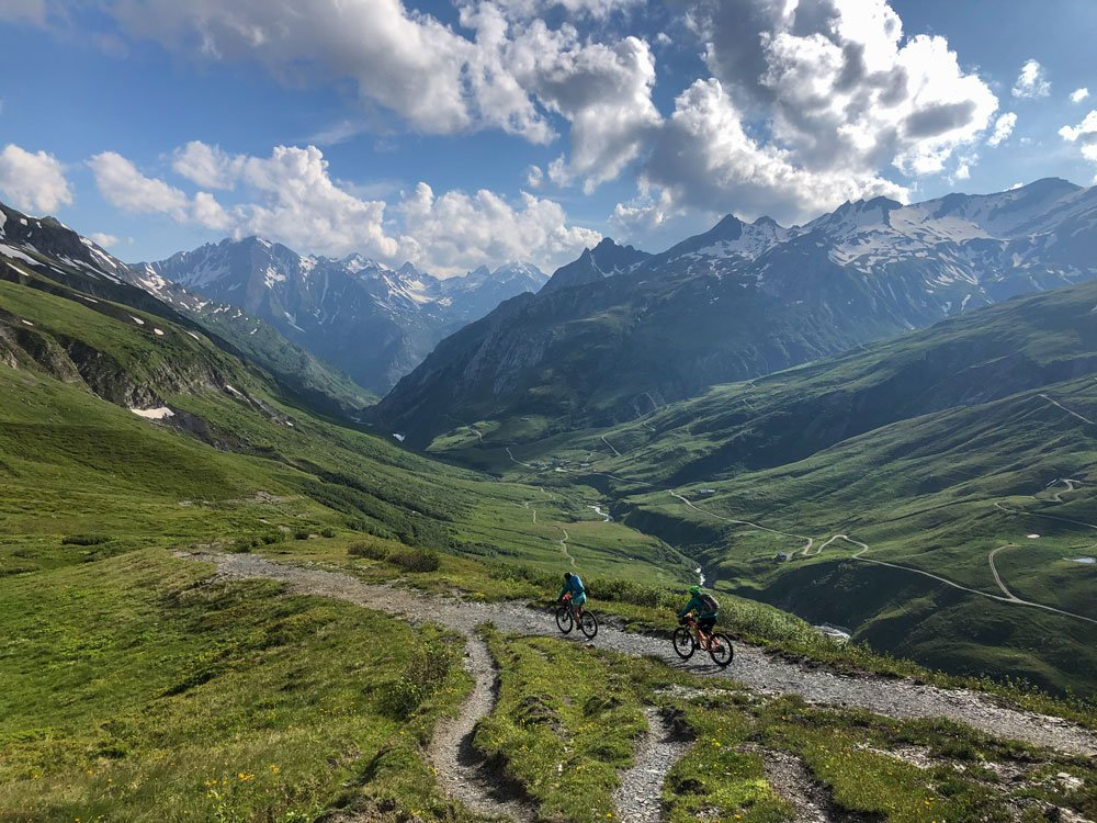 two cyclists descending a mountain trail