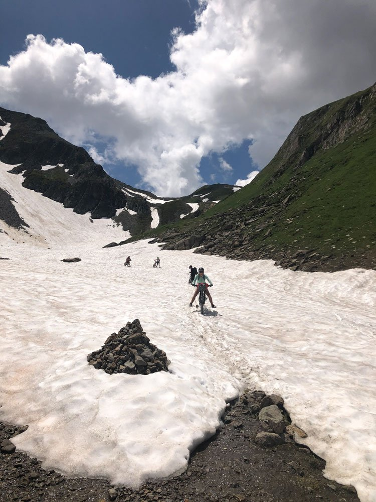 Cyclists crossing snow patches