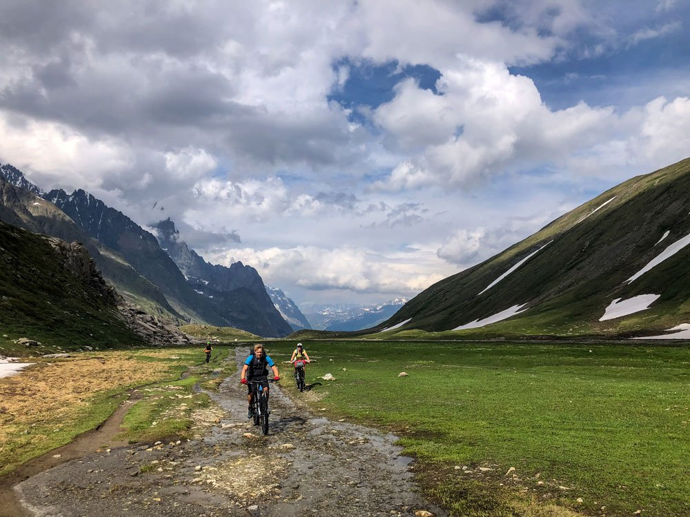 three mountain bikers cycling up a valley