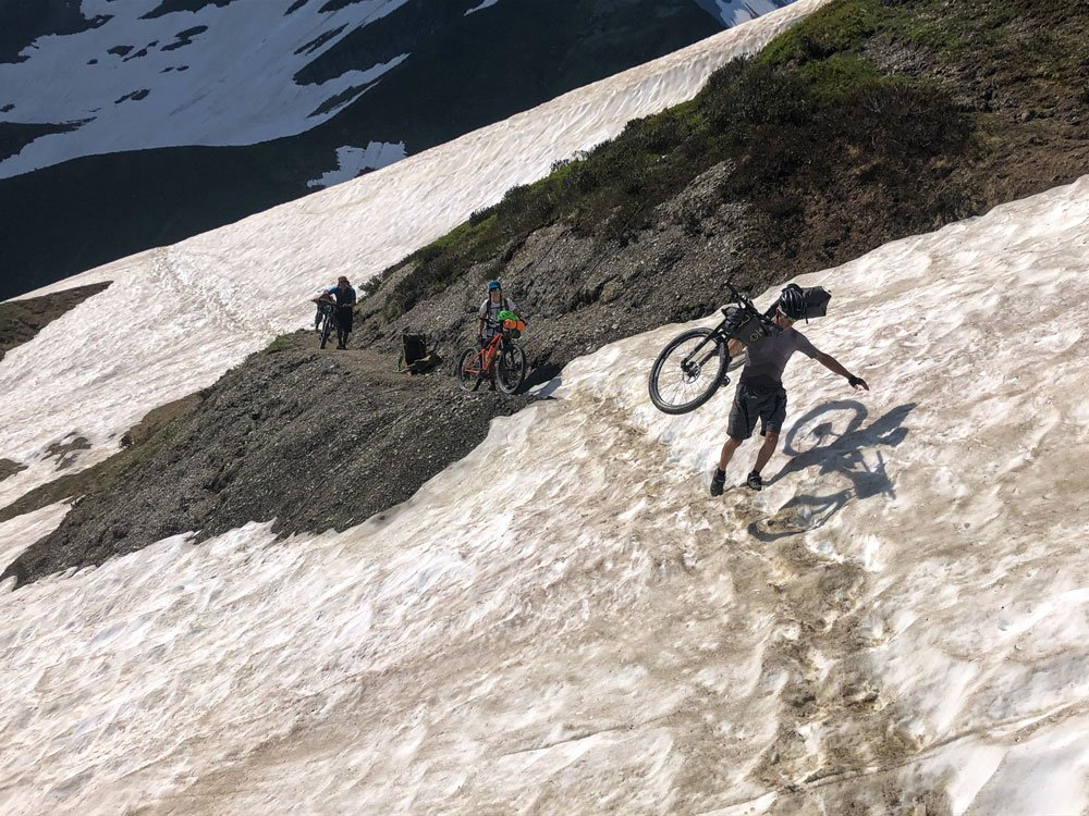 Cyclist carrying his bike over a snow patch