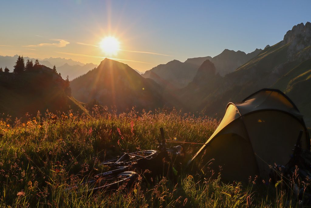 Tent on a mountain top at sunrise