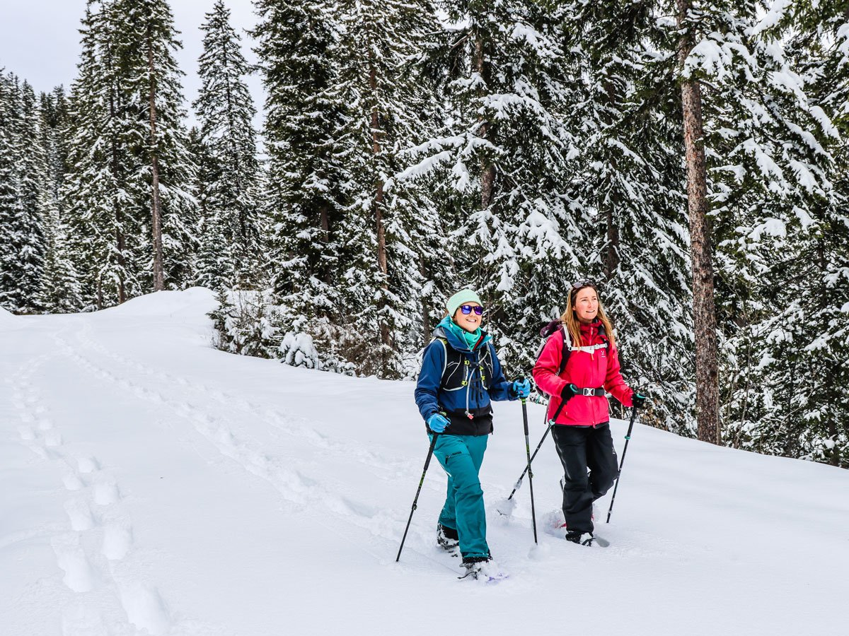 two girls snowshoeing in the forest